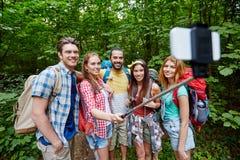 Amigos con la mochila que toma el selfie por smartphone Imagen de archivo libre de regalías