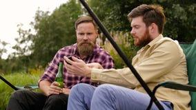 Amigos con la pesca del smartphone y la cerveza de consumición almacen de video