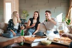 Amigos con la pizza, el vino y la cerveza hablando y divirtiéndose fotos de archivo libres de regalías