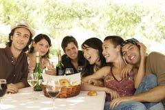 Amigos con las bebidas y cesta del pan en la tabla que disfrutan del partido Imagen de archivo libre de regalías