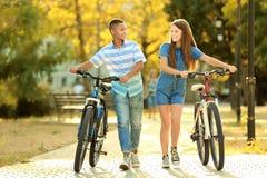 Amigos con las bicicletas que caminan en parque el día soleado Fotografía de archivo