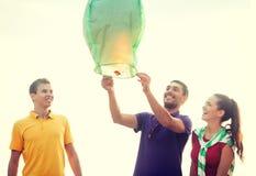 Amigos con las linternas chinas del cielo en la playa Imagenes de archivo