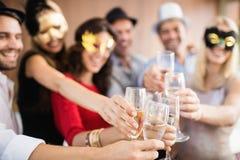Amigos con las máscaras en sostener los vidrios del champán Imágenes de archivo libres de regalías