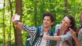 Amigos con las mochilas que caminan y que toman el selfie almacen de metraje de vídeo