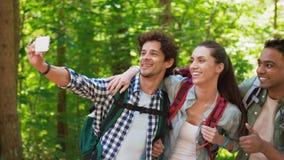 Amigos con las mochilas que caminan y que toman el selfie almacen de video