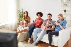 Amigos con los artilugios y la cerveza que ven la TV en casa Foto de archivo libre de regalías