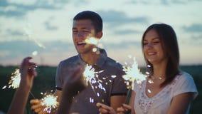 Amigos con los fuegos artificiales en sus manos que se divierten en un partido en la tarde vídeo de la cámara lenta