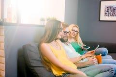 Amigos con los teléfonos en casa Imagen de archivo