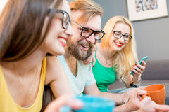 Amigos con los teléfonos en casa Foto de archivo libre de regalías