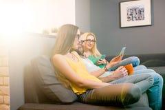 Amigos con los teléfonos en casa Imagen de archivo libre de regalías