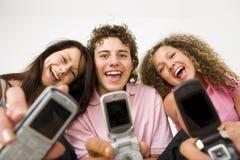 Amigos con los teléfonos móviles Fotos de archivo libres de regalías