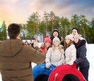 Amigos con los tubos de la nieve que toman la foto por la PC de la tableta fotos de archivo libres de regalías