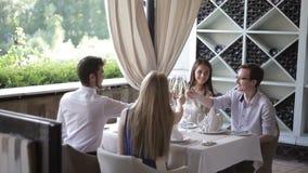 Amigos con los vidrios del champange que celebran y que tuestan en restaurante almacen de video