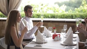 Amigos con los vidrios del champange que celebran y que tuestan en restaurante metrajes