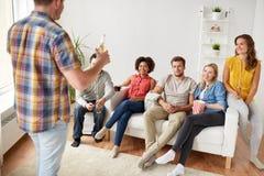 Amigos con palomitas y bebidas que hablan en casa Imagen de archivo