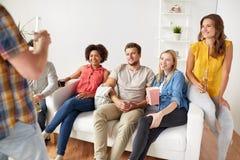 Amigos con palomitas y bebidas que hablan en casa Fotos de archivo