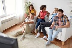 Amigos con palomitas y cerveza que ven la TV en casa Imagenes de archivo