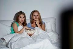 Amigos con palomitas y la TV de observación en casa Fotos de archivo