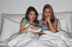Amigos con palomitas y la TV de observación en casa Fotografía de archivo libre de regalías