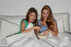 Amigos con palomitas y la TV de observación en casa Foto de archivo libre de regalías