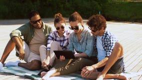 Amigos con PC de la tableta en el embarcadero en el lago o el río metrajes