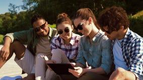 Amigos con PC de la tableta en terraza de madera en verano almacen de video