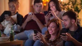 Amigos con smartphone que ven la TV en casa almacen de metraje de vídeo