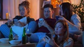 Amigos con smartphone que ven la TV en casa almacen de video