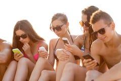 Amigos con smartphones en la playa Imagen de archivo libre de regalías
