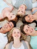 Amigos con sus cabezas junto que sonríen Imagen de archivo libre de regalías
