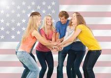 Amigos con sus manos apiladas contra bandera americana en fondo Foto de archivo