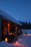 Amigos da casa de campo do inverno do por do sol que apreciam o nivelamento Imagens de Stock