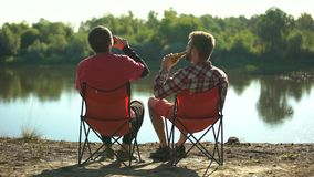 Amigos da infância que sentam-se no banco de rio, cerveja bebendo e discutindo a pesca video estoque