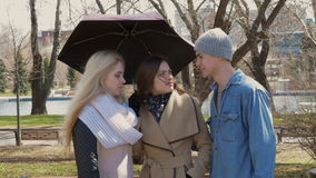Amigos da reunião no parque Duas meninas louras e um suporte moreno sob um guarda-chuva quando chover Um homem novo vídeos de arquivo