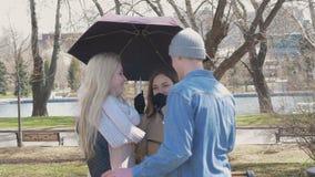 Amigos da reunião no parque Duas meninas louras e um suporte moreno sob um guarda-chuva quando chover Um homem novo filme