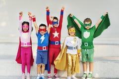 Amigos das crianças dos super-herói que jogam o conceito do divertimento da unidade fotos de stock royalty free