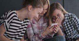 Amigos de adolescente que tienen contenido de observación de los medios de la diversión en el teléfono móvil
