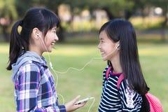 amigos de adolescentes que miran el teléfono elegante en escuela Imagenes de archivo