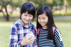 amigos de adolescentes que miran el teléfono elegante en escuela Foto de archivo libre de regalías
