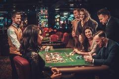 Amigos de la clase alta que juegan en un casino imagen de archivo