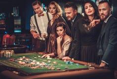 Amigos de la clase alta que juegan en un casino Imagen de archivo libre de regalías