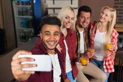 Amigos de la gente que toman la foto de Selfie que bebe el zumo de naranja, sentándose en el contador de la barra, teléfono de Sm Fotografía de archivo libre de regalías