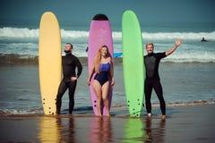 Amigos de la persona que practica surf en una playa con tableros que practican surf Imágenes de archivo libres de regalías