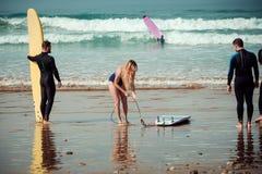 Amigos de la persona que practica surf en una playa con tableros que practican surf Fotos de archivo libres de regalías