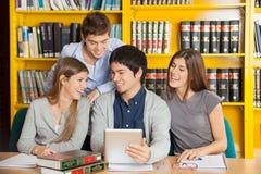 Amigos de la universidad con la tableta de Digitaces que estudian adentro Fotos de archivo libres de regalías