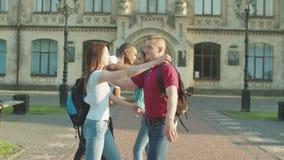 Amigos de la universidad que abrazan decir adiós al aire libre almacen de metraje de vídeo