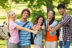 Amigos de la universidad que gesticulan los pulgares para arriba en campus Imagen de archivo