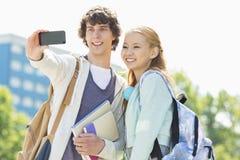 Amigos de la universidad que toman el selfie con el teléfono elegante en el campus Foto de archivo libre de regalías
