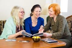Amigos de las mujeres adultas que se ríen de las fotos viejas imagen de archivo libre de regalías