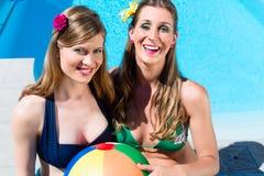 Amigos de las mujeres con la bola del agua que descansa en la piscina Imagen de archivo